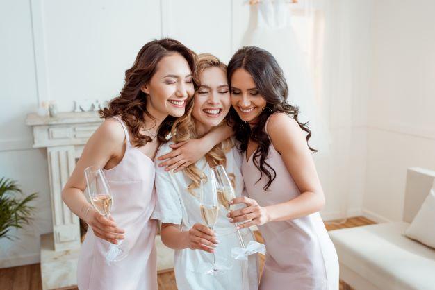 bridesmaids hugging bride on her wedding day